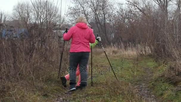 Glückliche Seniorinnen haben Spaß und Schwertspiel auf Nordic-Walking-Stöcken