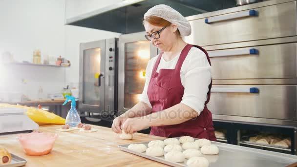 Erwachsene Art lächelnde Frau backt und bilden Fleischpasteten in der Bäckerei