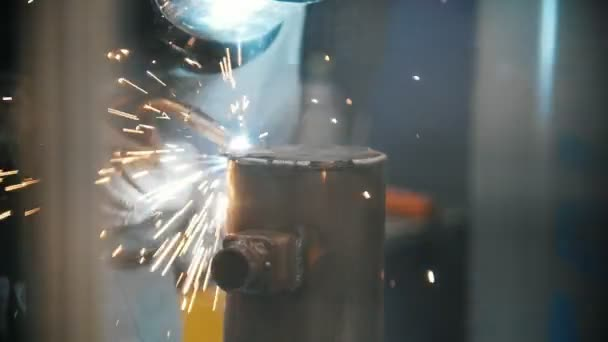 Svářeč svary kovových dílů v závodě, průmyslové svařování