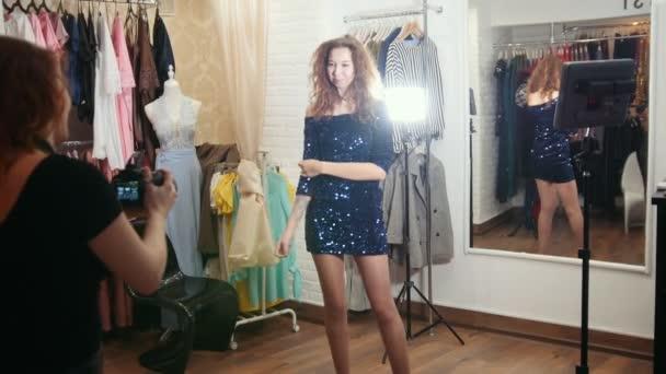 Krásná žena s kudrnaté vlasy ve večerních šatech pózování pro fotografa v butiku obchod oblečení