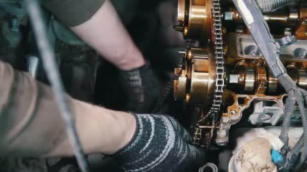 Mechanik demontuje motor auta, autoservis, demontáž motoru, práce v dílně