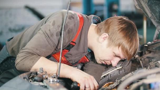 Mechanik s lampou zkontroluje a opraví automobilových motorů, autoopravárenství, práce v dílně, pracovat pod kapotou