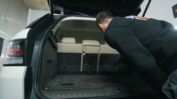 Mladík čistí vnitřek vozu s vakuum čistší, čištění kufru