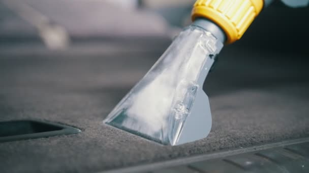 car interior cleaning with vacuum cleaner carpeted in the trunk