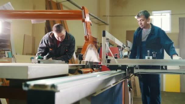 Dělníci tesaři jsou řezání dřevěných detailů na elektrická řetězová pila v továrně na nábytek