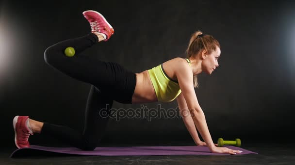 Fitness woman in sports clothing training for abdominal - lifts up legs