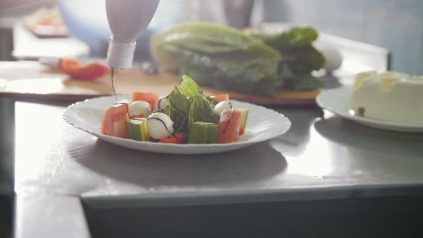 Šéfkuchař připravuje Řecký salát na talíři v restauraci