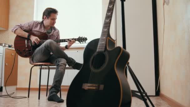 attraktiver junger Musiker komponiert Musik auf der Gitarre, anderes Musikinstrument im Vordergrund