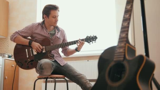 attraktiver junger Musiker komponiert Musik auf der Gitarre und spielt, anderes Musikinstrument im Vordergrund