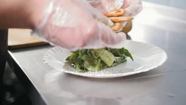 Rukou šéfkuchaře v kuchyni - Příprava salátu v komerční kuchyni nebo restaurace