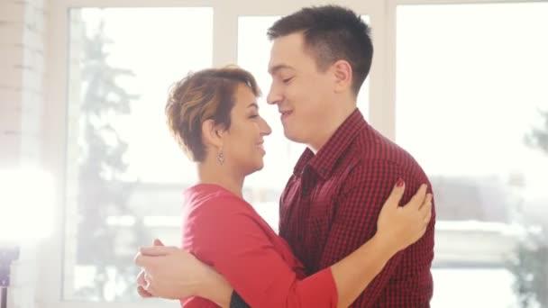 glückliches und attraktives verliebtes Familienpaar tanzt gemeinsam im Studio