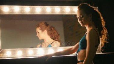 Sensual blonde woman in blue underwear posing near mirror