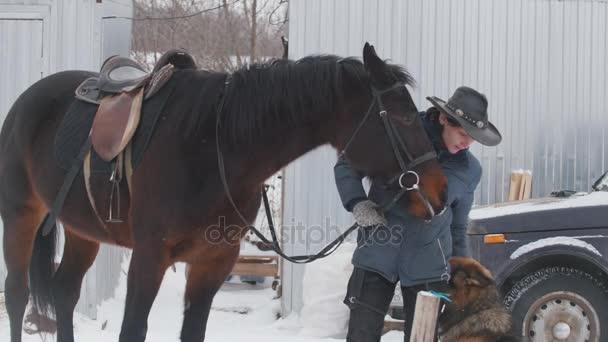 Žena v kovbojském klobouku s koně a psa stojí na sněhové pole
