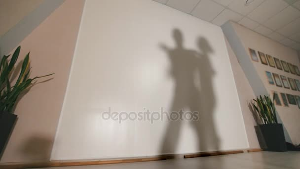 Shadow of man and woman dancing and rehearsing Latin American dance in costumes, slow motion