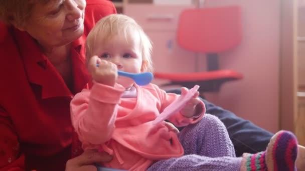 Malá holčička a její babička hraje s hračkami a hladit něžně sedí na podlaze