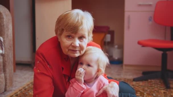 Malá dívka si hraje s její babičkou na podlaze, babička objímání a líbání vnučka