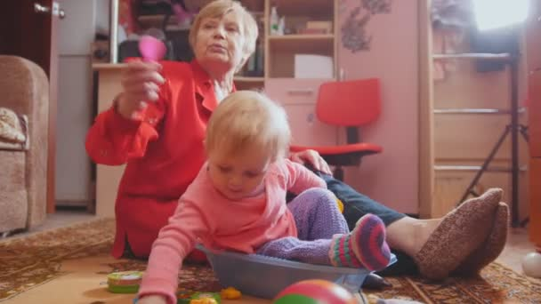 Malá holčička a její babička hraje s hračkami a komunikaci, něžně sedí na podlaze