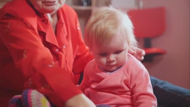 Roztomilá holčička a její pěkný babička hraje s barevné hračky