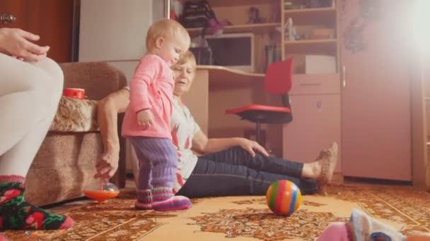 Malá dívka si hraje s její babičkou na podlaze, hračky, míč a panenka v popředí