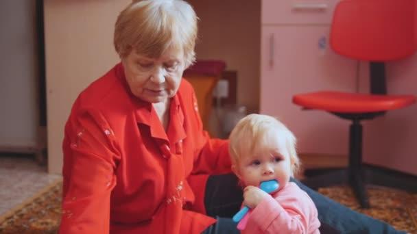 Malá holčička a její babička hraje s hračkami, které sedí na podlaze