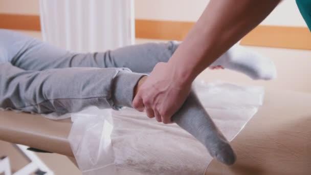 Chiropratico che massaggia una giovane donna sdraiata su un lettino da massaggio, stretching suoi piedi