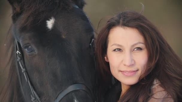Portrét krásné ženy jezdec a černého koně v zimě oboru