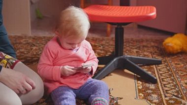The little girl looking at the smartphone with her mother showing her how to use the gadget