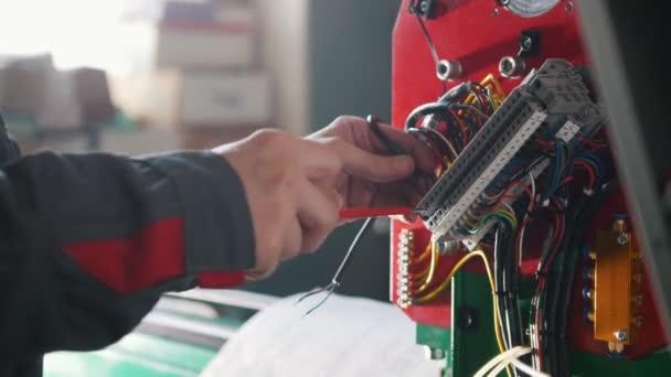 Elektriker übergeben die Installation eines Energiesystems an die Maschinenindustrie