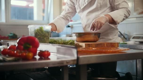 Šéfkuchař připravuje salát přidáním bylin a koření, zeleninu v popředí