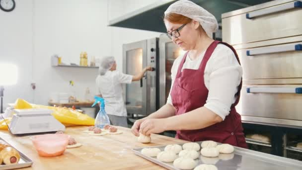 Woman in glasses and apron bakes cakes in the bakery
