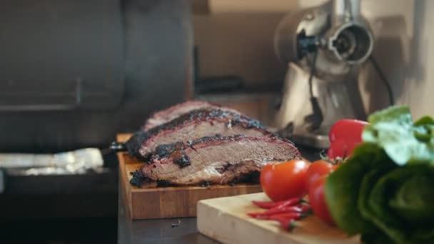 Dva velké kusy masa uzené hrudí na dřevěném prkénku
