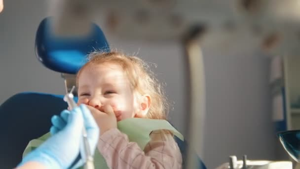 Malá roztomilá holka v kanceláři zubaři nechce léčit, odolávání a zavírání úst s rukama