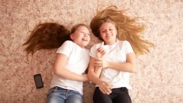 Dvě teenky ležící na podlaze, jejich vlasy šíří po podlaze