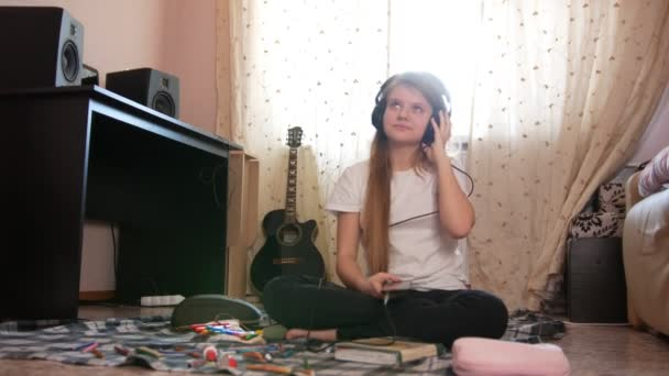 Dospívající dívka poslechu hudby ve sluchátkách pomocí smartphone sedí na podlaze doma
