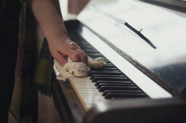 The old ladys hand wiping the dust off the piano keys with a cloth