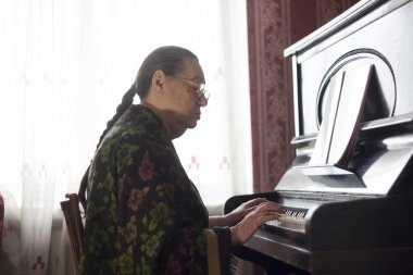 The old lady playing classical music on the rarity piano at home