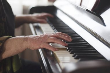 The old ladys hands playing classical music on the piano at home