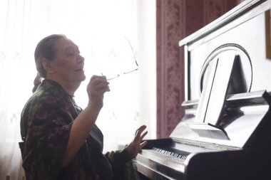 The old lady sitting in front of a piano and singing a song looking into a notebook