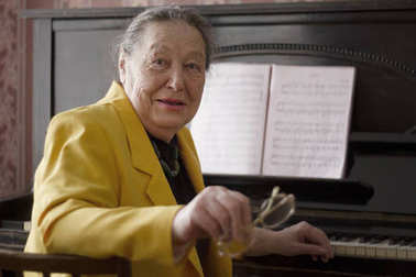 Old charming lady pianist in the yellow jacket seating at the piano with glasses in her hands