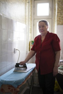 Elderly woman in the red blouse ironing a towel at home