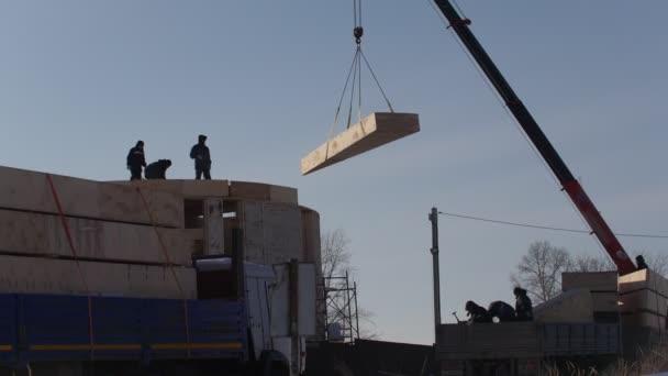 Práce stavební jeřáb zvedá slámy dřevěný blok pro kruh ekologie dům