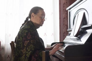 The old lady playing the piano at home