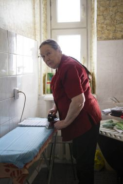 Old lady in the red blouse ironing a towel at home