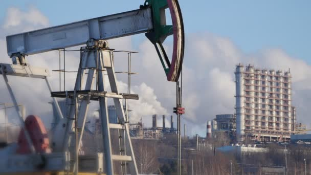Close-up of a running pump for the extraction of crude oil and of a petrochemical plants pipes emissions