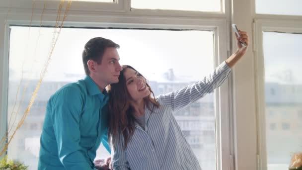 Mladá a atraktivní muž a žena, která dělá selfie sedět u okna