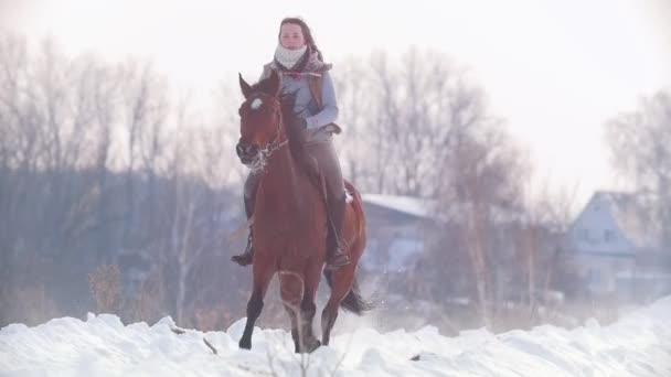 Dlouhovlasého ženy jezdec rychle a divoce na černém koni sněhem, pomalý pohyb