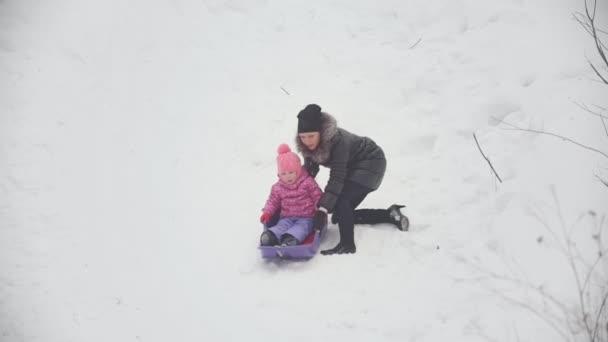 Mutter zieht einen Schlitten, in dem ihre lustige Tochter liegt