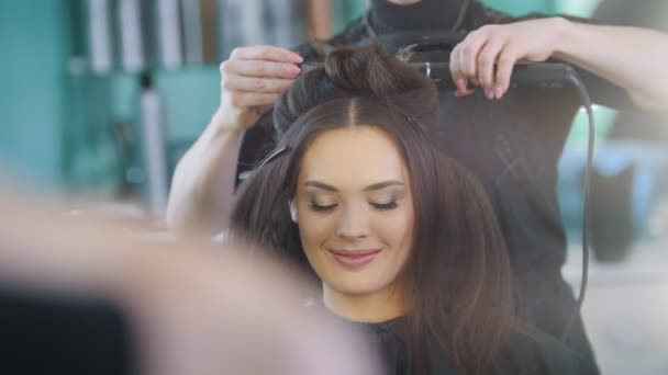 Professional hairstylist creating evening hairstyle for beautiful smiling model