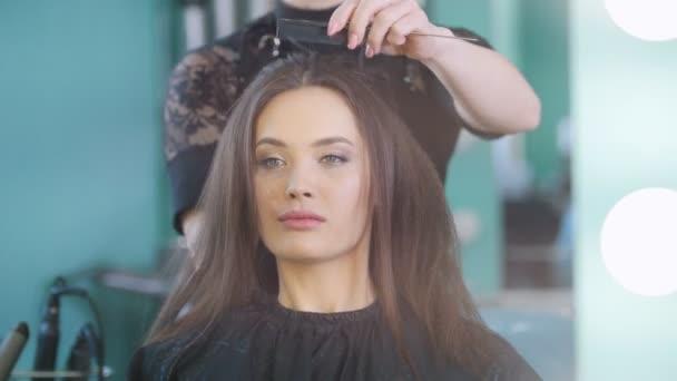 Professzionális fodrász, esti frizura vonzó mosolygó modell létrehozása