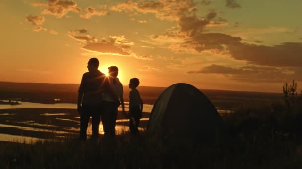 Mladá zdravá rodina - otec, matka a syn v kempu - stojí na vysokém kopci na letní západ slunce a při pohledu na horizont